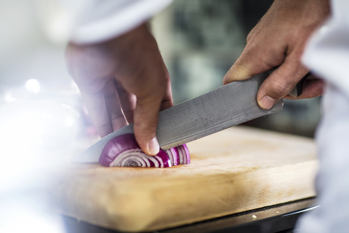 Chef slicing red onion, close-up